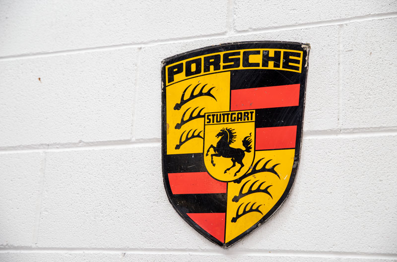Porsche Logo on white brick wall
